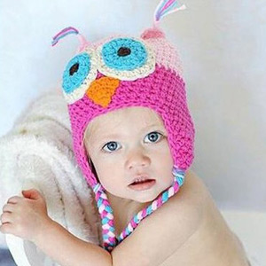 An image of a baby girl wearing a pink and brown owl hat